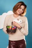 拿着白色小的复活节兔子的美丽的妇女取暖鸡蛋 库存照片