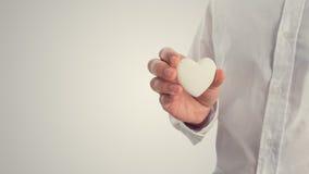 拿着白色心脏的一个人的减速火箭的图象 免版税库存图片