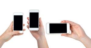 拿着白色智能手机的手 免版税库存照片