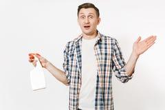 拿着白色有擦净剂液体的方格的衬衣的年轻管家人空白空的清洗的浪花瓶被隔绝  库存图片