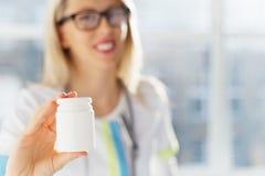 拿着白色未贴标签的医学药瓶的医生 图库摄影