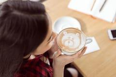 拿着白色杯子和喝与装饰熊的方格的衬衣的年轻深色的妇女热奶咖啡咖啡 免版税库存图片