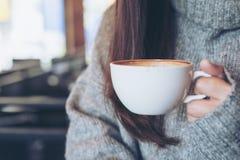 拿着白色杯子热的咖啡的妇女坐在冬时的咖啡馆 库存照片