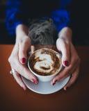 拿着白色杯子用热的咖啡的女性手 免版税库存照片