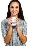 拿着白色杯子的可爱的妇女微笑对照相机 库存图片