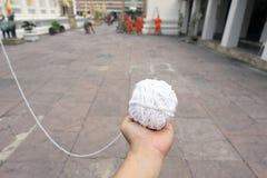 拿着白色神圣的绳索的手是在佛教和泰国文化扮演重要作用和是祷告的标志 免版税库存图片