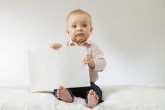 拿着白色空白的男婴 坐与海报的婴儿孩子在他的手上 嘲笑 复制空间 明信片的想法 免版税库存图片