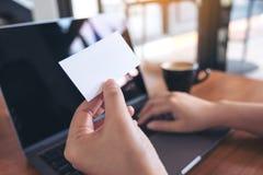 拿着白色空的名片的手,当使用有咖啡杯的膝上型计算机在木桌上时 免版税库存照片