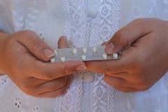 拿着白色药片的天线罩包装千福年的妇女 免版税库存图片