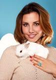 拿着白色蓬松小的兔子的美丽的白肤金发的妇女 图库摄影