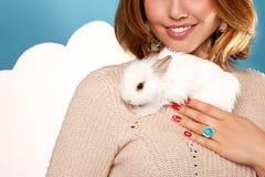拿着白色蓬松小的兔子的美丽的白肤金发的妇女 免版税库存照片