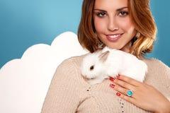 拿着白色蓬松小的兔子的美丽的白肤金发的妇女 库存照片