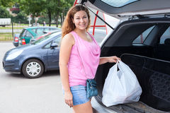 拿着白色袋子的微笑的妇女有很多在她的汽车之后的杂货 免版税库存图片