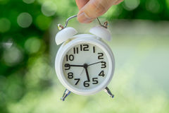 拿着白色闹钟的手作为企业或时间读秒骗局 免版税库存照片