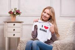 拿着白色婴孩紧身衣裤的年轻可爱的妇女 免版税库存照片