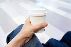 拿着白色disposadle纸咖啡的妇女手 库存照片