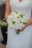 拿着白花的美丽的婚礼花束新娘 免版税库存照片
