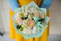拿着白花的花束女孩 免版税库存照片