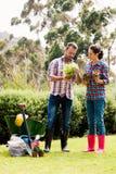 拿着盆的植物的全长夫妇在草坪 免版税库存图片
