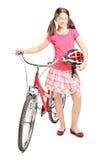 拿着盔甲和推挤自行车的十几岁的女孩 免版税图库摄影