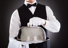 拿着盘子和盒盖的男性侍者 库存照片