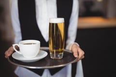 拿着盘子用咖啡和啤酒杯的女服务员的中央部位 图库摄影