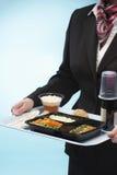 拿着盘子用飞机食物的空中小姐 免版税库存图片
