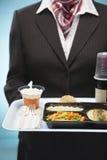 拿着盘子用飞机食物的空中小姐 免版税图库摄影