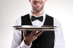 拿着盘子的侍者 微笑的男管家 库存照片