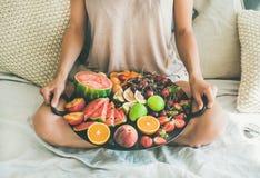 拿着盘子的女孩有很多新鲜的季节性果子 免版税库存照片