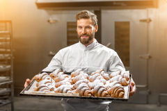 拿着盘子的英俊的面包师有很多新近地被烘烤的croisants 免版税库存照片