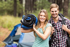 拿着睡袋和背包的一对年轻俏丽的远足者夫妇的画象 库存照片