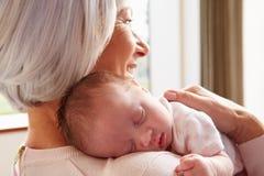 拿着睡觉的新出生的小孙女的祖母 库存照片