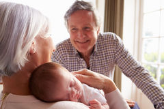拿着睡觉的新出生的小孙女的祖父母 免版税库存照片