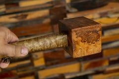 拿着短槌锤子的人手由节木工具制成用于由木匠车间在被弄脏的背景 免版税图库摄影