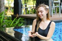 拿着石标小组石头的妇女,做在swimm的瑜伽平衡 免版税图库摄影