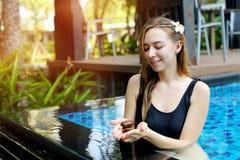 拿着石标小组石头的妇女,在游泳池阳光下做瑜伽平衡 免版税库存照片