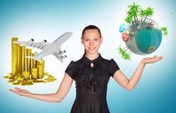拿着硬币和地球地球的女实业家 免版税图库摄影