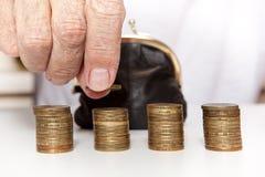 拿着硬币和小金钱囊的老资深手 库存图片