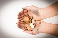 拿着硬币的两只肮脏的妇女手被隔绝在白色背景 库存图片