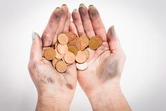 拿着硬币的两只肮脏的妇女手 免版税库存图片