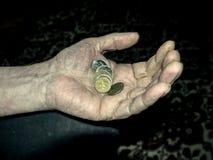 拿着硬币的起皱纹的手 免版税库存照片