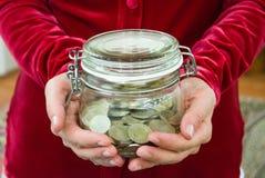拿着硬币被填装的玻璃瓶子的妇女 库存照片