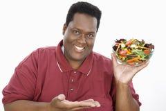 拿着碗沙拉的一个肥胖人 免版税库存图片