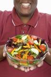 拿着碗沙拉的一个肥胖人 库存图片