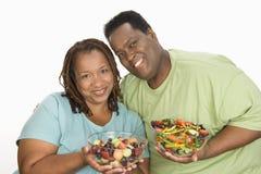 拿着碗沙拉的肥胖夫妇 免版税库存照片