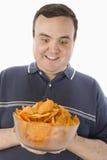 拿着碗烤干酪辣味玉米片的激动的人 库存照片