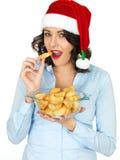 拿着碗煮熟的烘烤土豆的圣诞老人帽子的少妇 库存图片