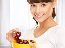 拿着碗用樱桃的健康妇女 图库摄影