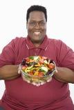 拿着碗菜沙拉的一个肥胖人 免版税图库摄影